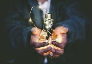 male hands holding Edison lightbulb